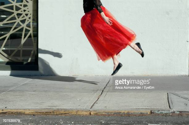 woman with red skirt in mid-air - jupe photos et images de collection
