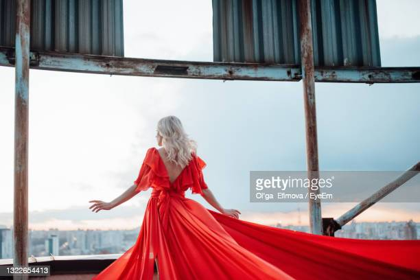 woman with red umbrella standing by window - evening gown stock pictures, royalty-free photos & images