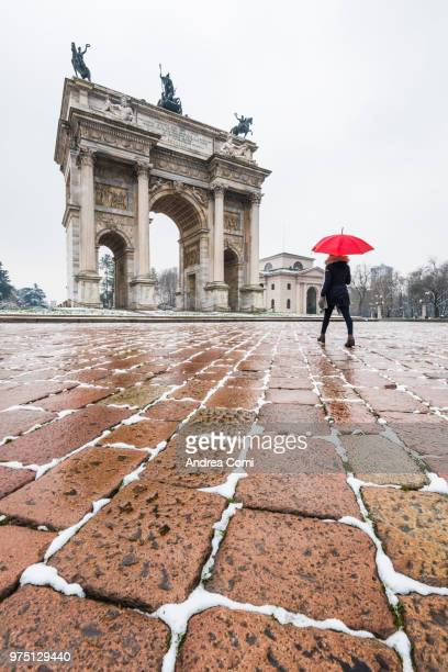 Woman with red umbrella walks near the Arch of Peace during a snowfall. Milan, Lombardy, Italy