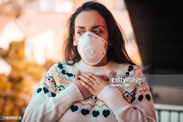 woman with respiratory mask out in polluted city - irritation stock pictures, royalty-free photos & images