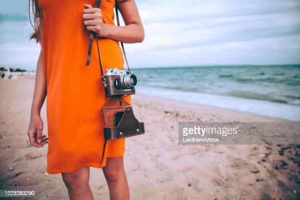 donna con telecamera retrò sulla spiaggia - henri coste foto e immagini stock