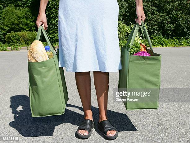 woman with reusable grocery bag in each hand - bag stock pictures, royalty-free photos & images