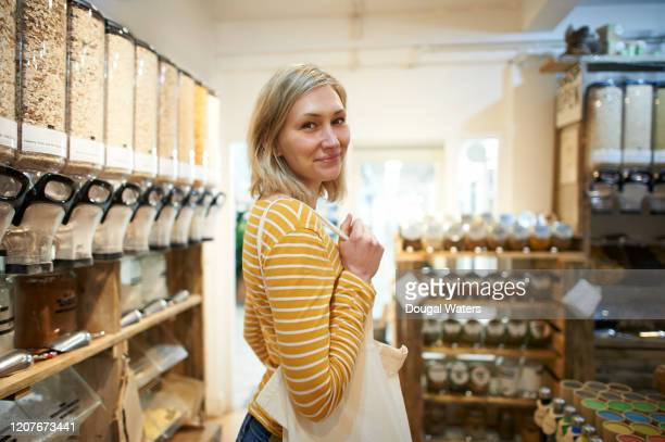 woman with reusable shopping bag in zero waste refill store. - questions environnementales photos et images de collection