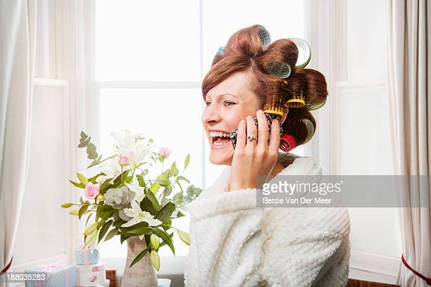 Woman with rollers in hair on mobile phone.