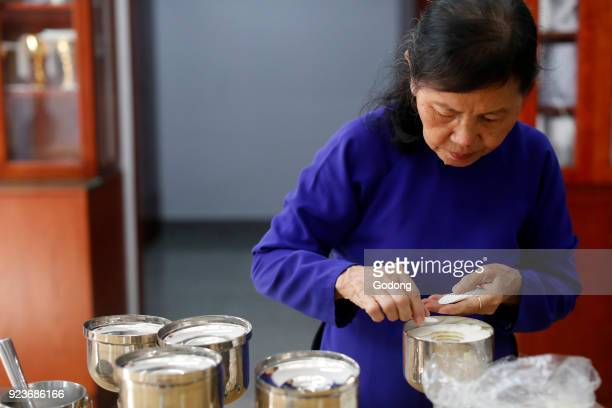 Woman with Roman Catholic unleavened wafers for the Holy Communion Our Lady of Fatima church Ho Chi Minh City Vietnam