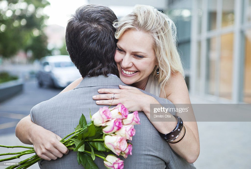 Woman with roses, hugging man, smiling : Stock Photo