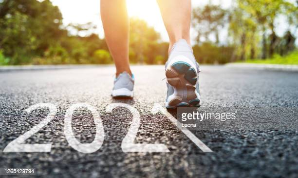 woman with running shoes standing and number 2021 on road - new year stock pictures, royalty-free photos & images
