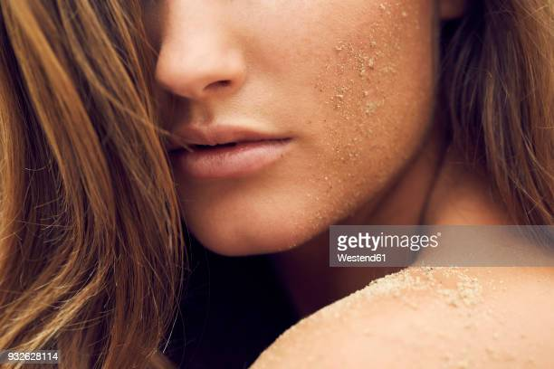 Woman with sand on her cheek, close-up