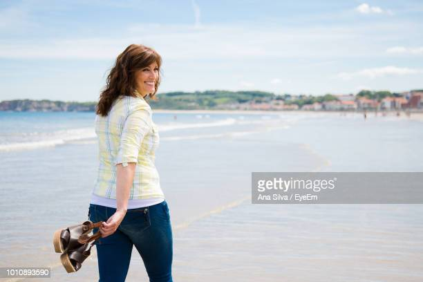 Woman With Sandals On Beach