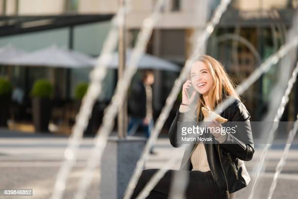 Woman with sandwich calling phone