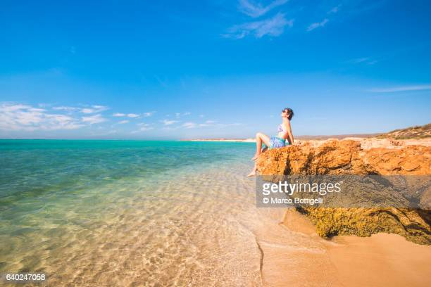 Woman with sarong and straw hat sunbathing at Osprey Bay, Cape Range National Park, Exmouth, Western Australia.
