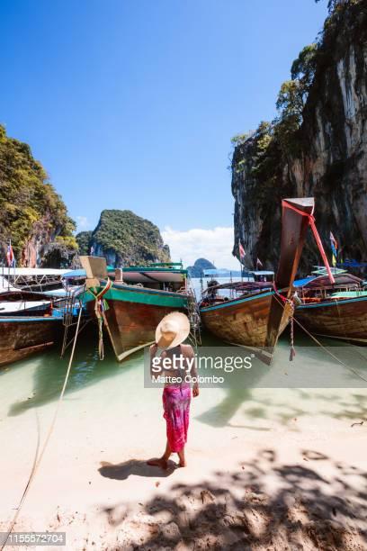 woman with sarong standing near longtail boats, krabi, thailand - railay strand stock-fotos und bilder