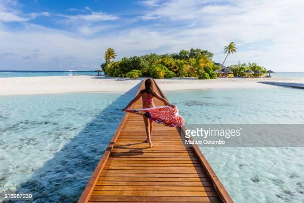 Woman with sarong walking on pier, Maldives