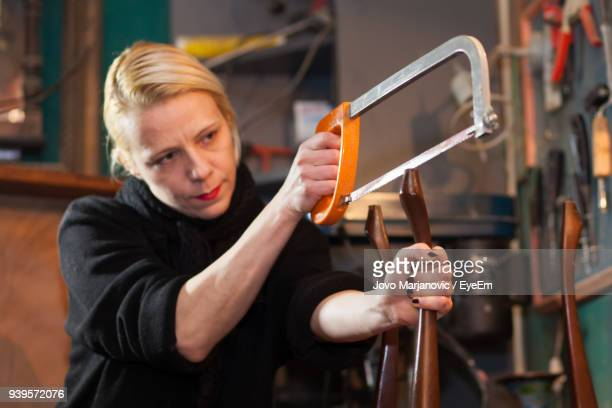 Woman With Saw Cutting Wood