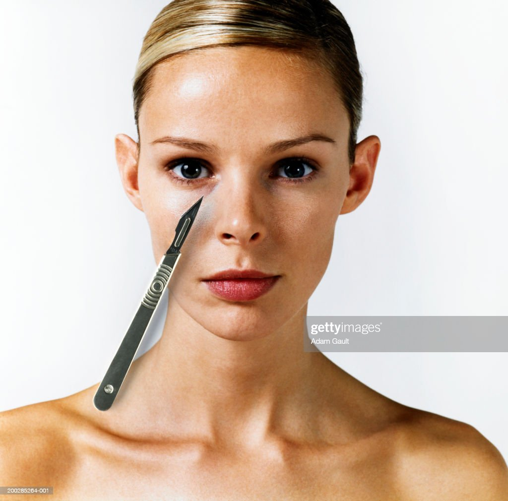 Woman with scalpel on right side of face, portrait : Stock Photo