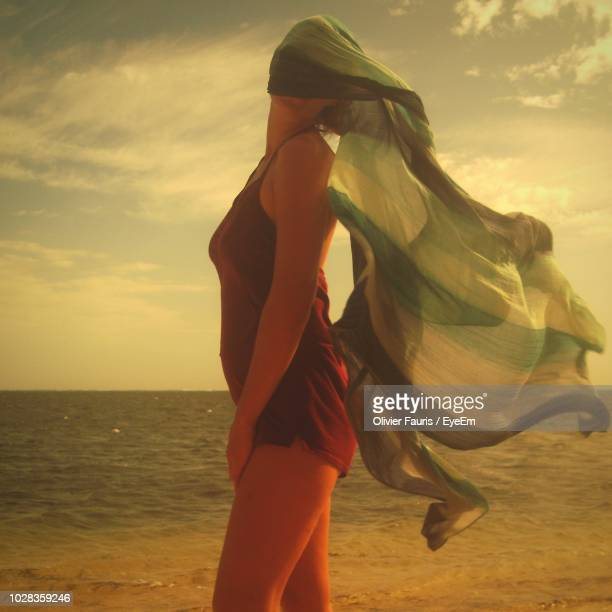 Woman With Scarf Standing At Beach Against Sky