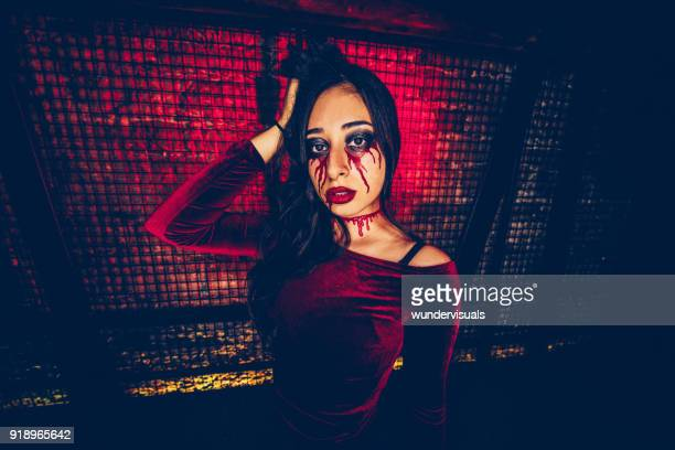 woman with scary make-up celebrating haloween at dungeon party - devil costume stock photos and pictures