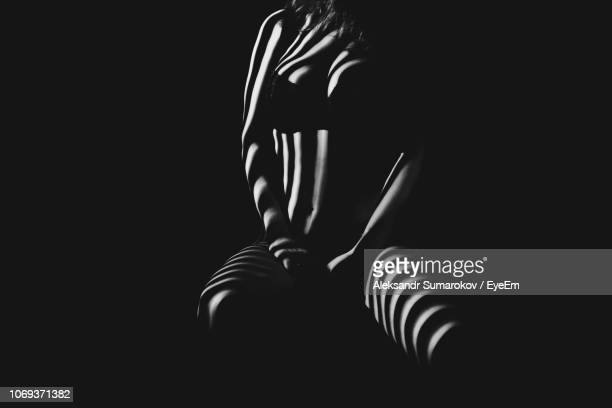 woman with shadow on body against black background - human body part ストックフォトと画像