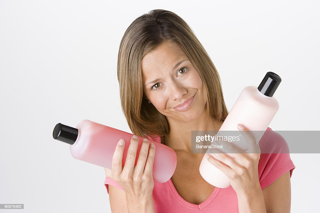 Woman with shampoo and conditioner : Stock Photo
