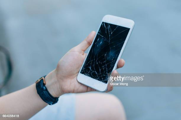 Woman with shattered cell phone