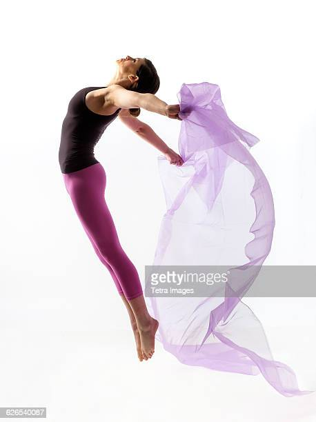 Woman with sheer fabric jumping
