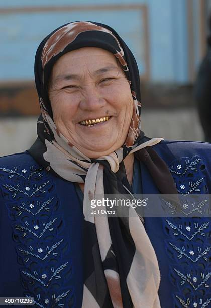 A woman with shiny gold teeth in front of the Kalyan Mosque part of the PoiKalyan an architectural complex in Bukhara Uzbekistan Former Soviet union...
