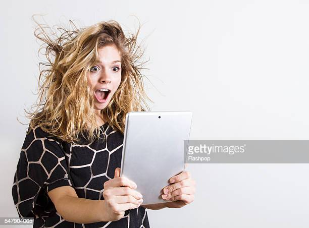 Woman with shocked expression using digital tablet