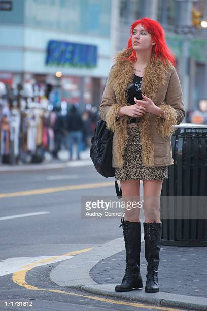 Woman with shocking red hair, leopard print skirt and black boots on corner in midtown Manhattan, New York City