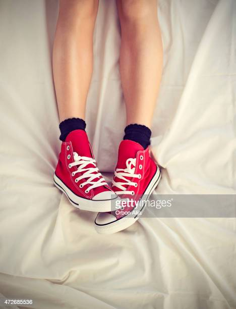 Woman with shoes on bed