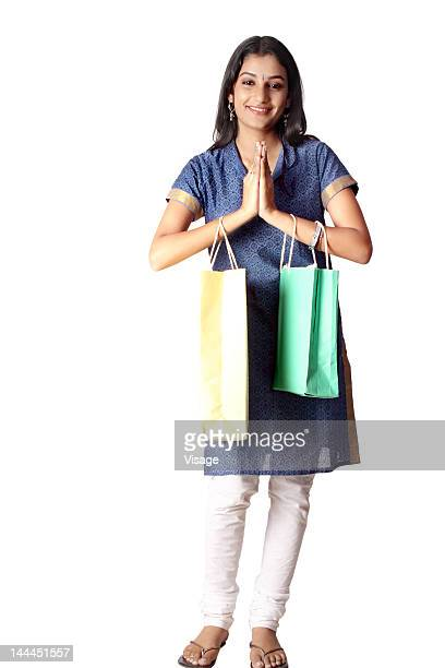 Woman with shopping bag and doing welcome gesture