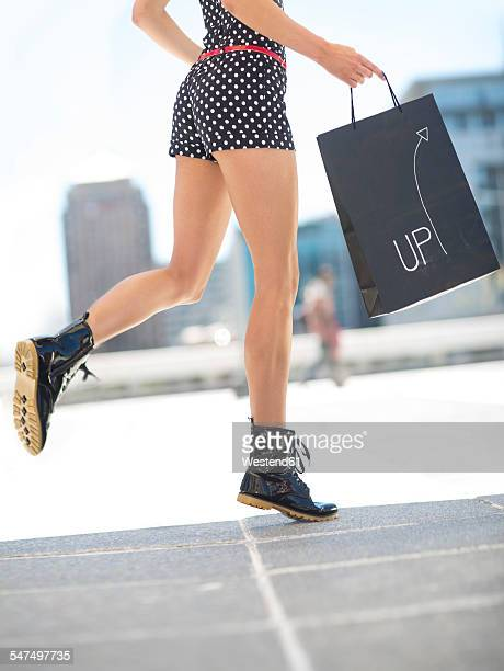 Woman with shopping bag wearing black patent leather boots