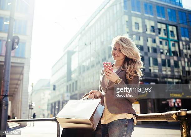Woman with shopping bags and smartphone.