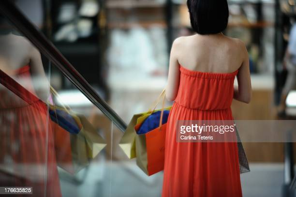 woman with shopping bags going down the escalator - strapless dress stock pictures, royalty-free photos & images