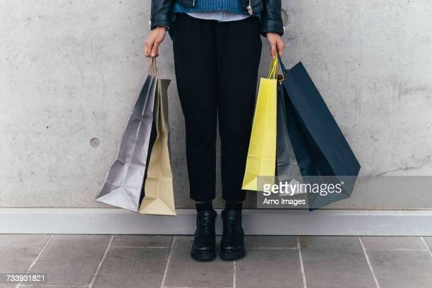 woman with shopping bags, grey wall background - shopping bag stock pictures, royalty-free photos & images