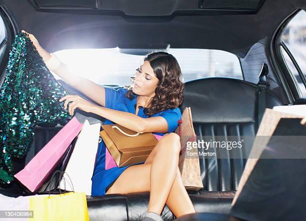 Mulher com sacos de compras em backseat de limo
