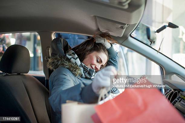 Woman with shopping bags in car