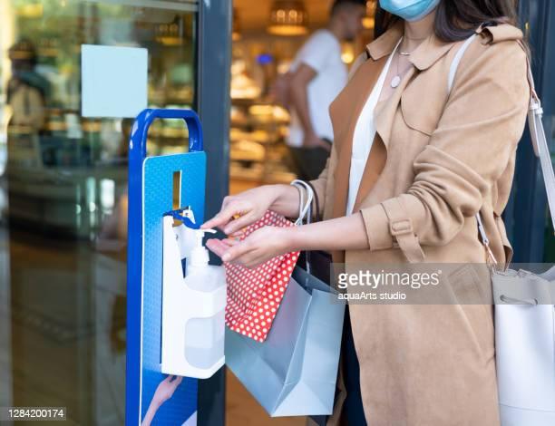 買い物袋を持つ女性は、レストランでウイルスに手を掃除するために消毒剤ゲルを使用しています - 消毒薬 ストックフォトと画像