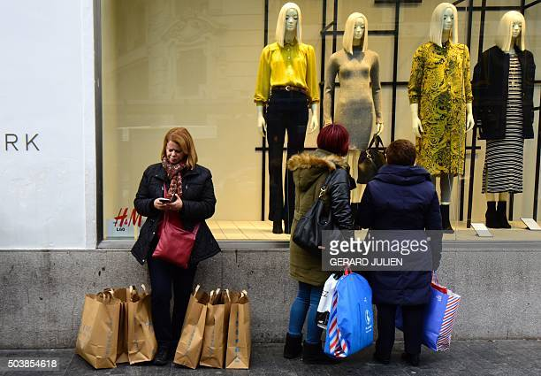 A woman with shopping bags looks at her mobile phone as others look at a shop window during the first day of the winter sales in Madrid on January 7...