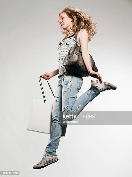 Woman with shopping bags running against grey background