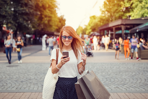 Woman with shopping bags texting in the city - gettyimageskorea
