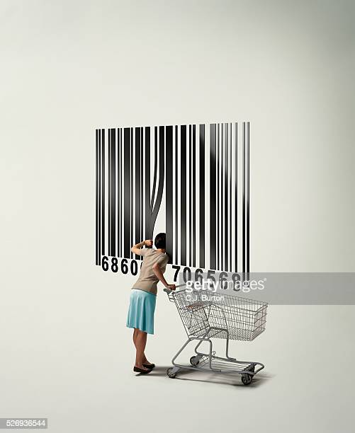 Woman with shopping cart looking inside giant barcode