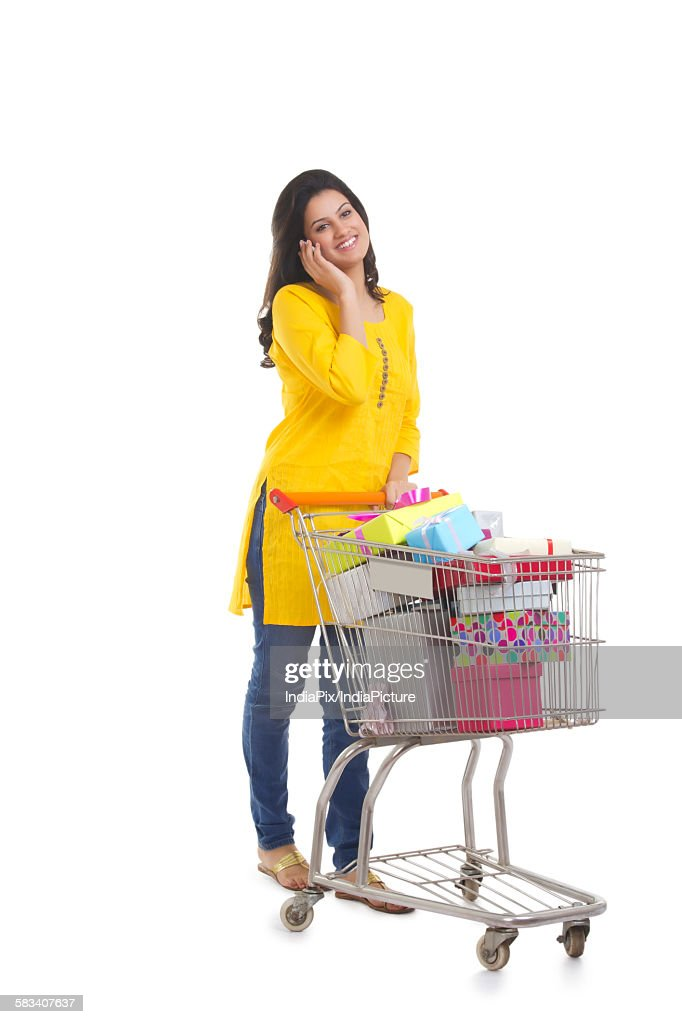 Woman with shopping cart talking on a mobile phone : Stock Photo