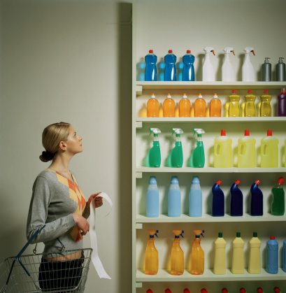 Woman with shopping list and basket looking at shelf display - gettyimageskorea