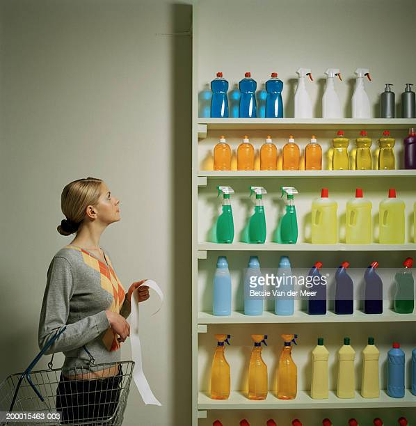 Woman with shopping list and basket looking at shelf display