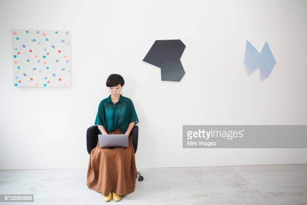woman with short black hair wearing green shirt sitting in art gallery, typing on laptop computer. - kunst kultur und unterhaltung fotos stock-fotos und bilder