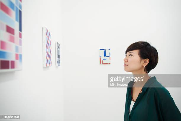 woman with short black hair wearing green shirt standing in art gallery, looking at modern painting. - kunst kultur und unterhaltung fotos stock-fotos und bilder