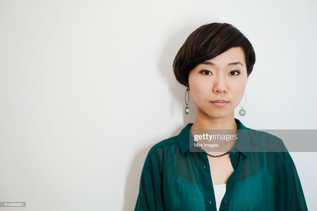 Woman with short black hair wearing green shirt standing in art gallery, looking at camera. : ストックフォト