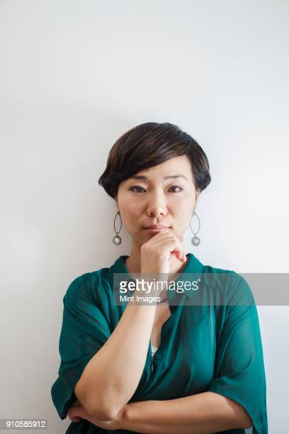 Woman with short black hair wearing green shirt standing in art gallery, hand on chin, looking at camera.