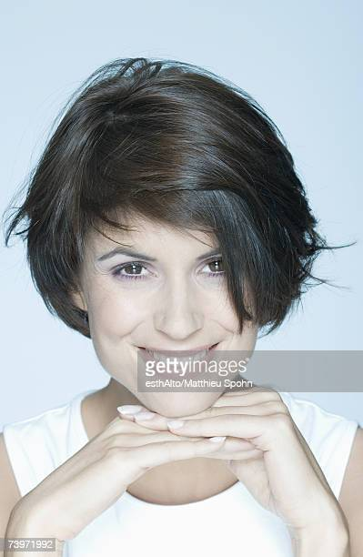 Woman with short hair, hands under chin, smiling, portrait