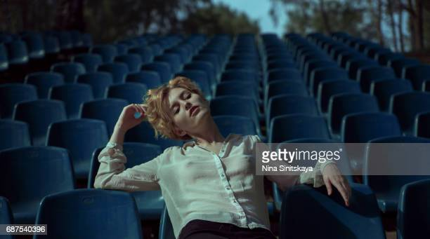 woman with short hair hanging out at blue stadium seats - blouse stockfoto's en -beelden